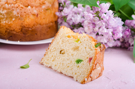 Slice of pannetone cake with cugar fruits and lilac flowers on spring background.