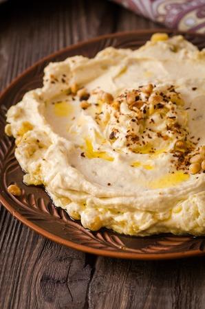 Plate of creamy hummus on wooden table.Ramadan food. Selective focus. Toned image