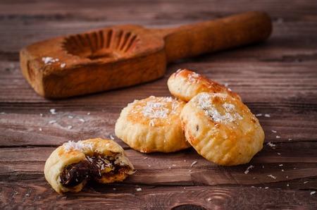 Maamoul または mamoul - アラビア語のクッキーはヴィンテージの木製テーブル背景に木型の近くのココナッツを使用して日付を詰めた。選択と集中。ト