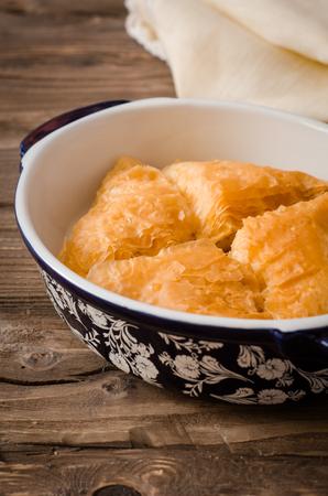 Homemade baklava stuffed cream with honey sirup on wooden table. Eastern sweets. Ramadan food