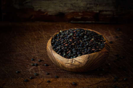 Raw Organic Black Lentils in wooden Bowl on dark background. Toned image
