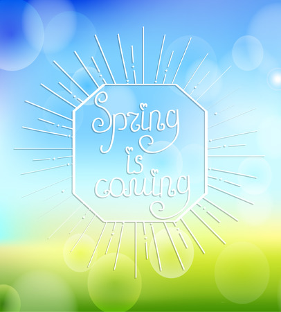 Sunburst with a calligraphical inscription of Its spring is coming on an abstract spring boceh background.