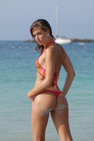 Girl in bikini in the seaside waiting for a boat Stock Photo