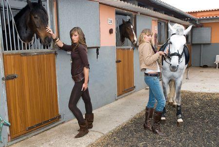 hispanique deux filles avec les chevaux dans l'écurie