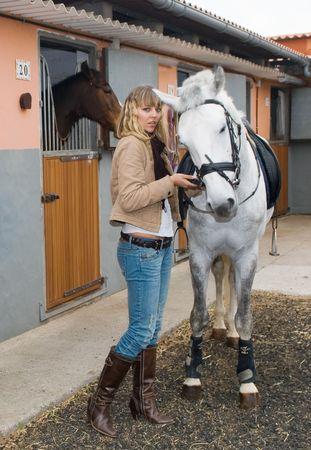 Jeune fille avec un cheval dans l'écurie