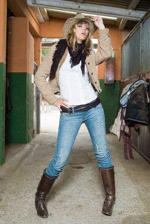 fashion cow girl in a horse stable