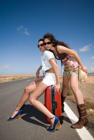 women on the road waiting for a  under the blue sky and with sun glasses Stock Photo