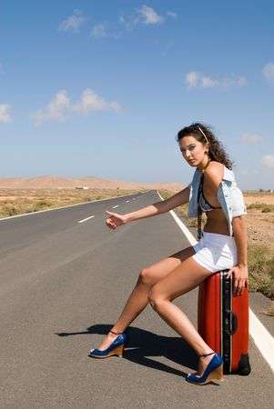 hitchhiking: woman on the road in auto-stop