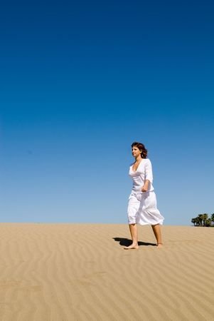Beautiful woman walking in the sand without shoes photo