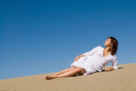 Beautiful woman lying in the sand with a white dress
