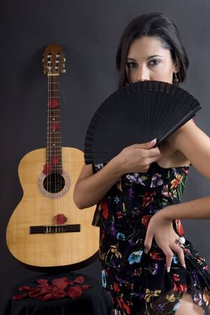 to observer: beautiful flamenco dancer with black background and guitar