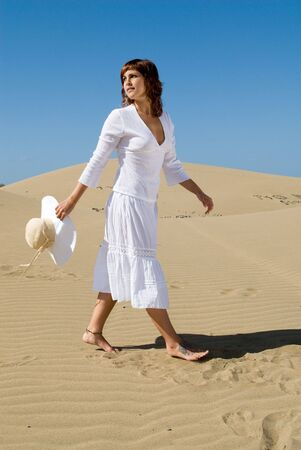 woman with hat and beauty dress in the dunes