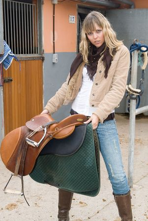 rein: Woman in an stable with jeans and a horse Stock Photo