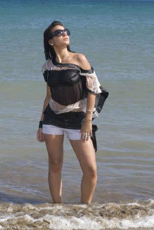 wet clothes: mujer en la orilla del mar con lentes de sol y ropa h�meda