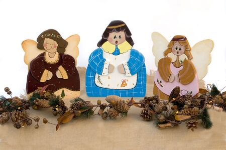 Three figurine christmas choir angels in wood isolated in white Stock Photo - 3789346