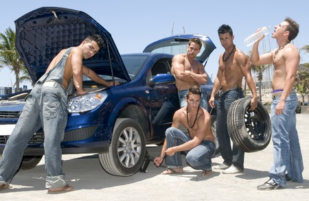 gay men: men changing a wheel under the sun