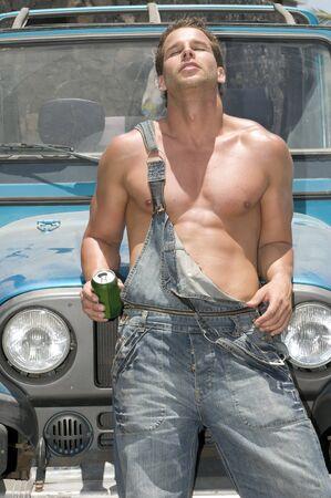 hombre tomando cerveza: sexy hombre bebiendo cerveza bajo el sol