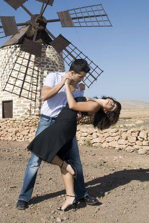 near: man and woman dancing a tango near an windmill