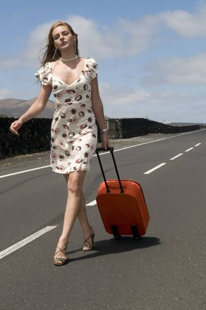 macadam: woman on the road with her suitcase Stock Photo