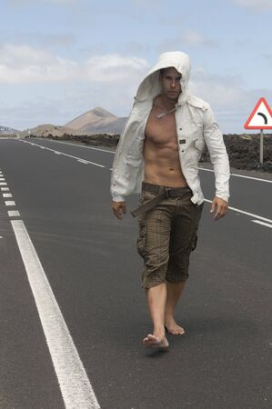 muscled: muscled man walking on the road without shoes Stock Photo