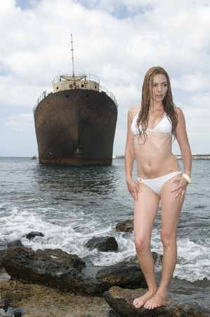 ship wreck: woman near an abandoned ship in bikini
