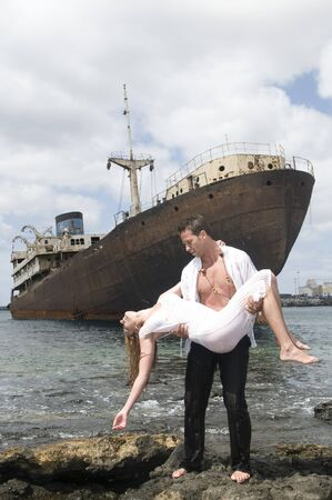 wreckage: man with a woman in arms near an abandoned ship under the sky Stock Photo