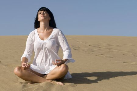 woman in the sand relaxing in meditation position Stock Photo - 4336672
