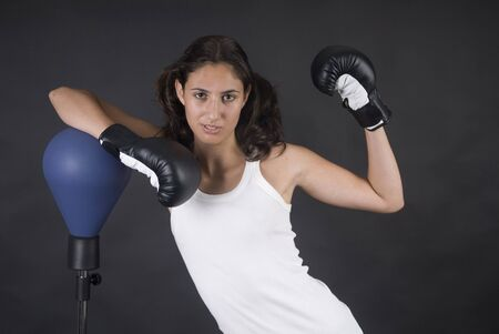 sportingly: Young beauty woman boxer fighting with punch bag