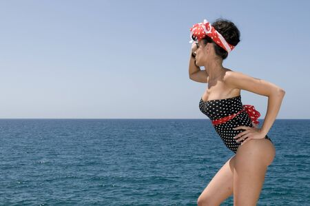 sexy pin up woman near the sea with copy space photo