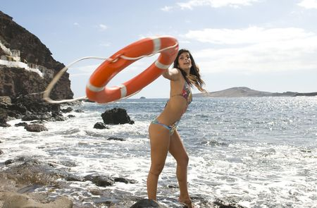 beautiful liveguard with an orange lifebuoy near the ocean photo