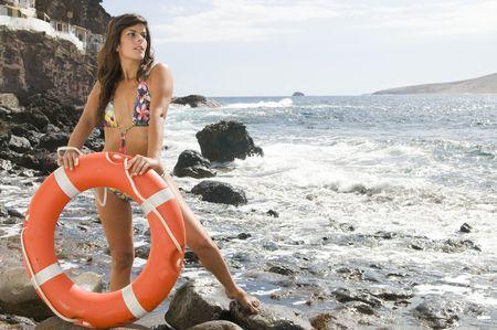 baywatch: beautiful liverguard in the beach with an orange lifebuoy