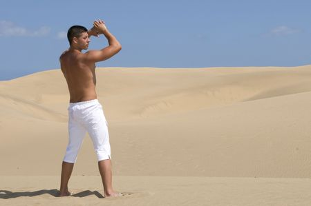 muscled: muscled man in the desert dunes with white trousers under the sun