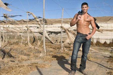muscled man with jeans laughing in desolated landscape Stock Photo