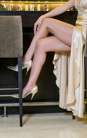 velvet dress: beautiful woman legs in a cocktail bar Stock Photo