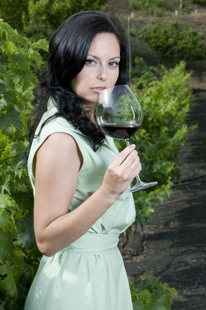 woman with red wine glass in a vineyard photo
