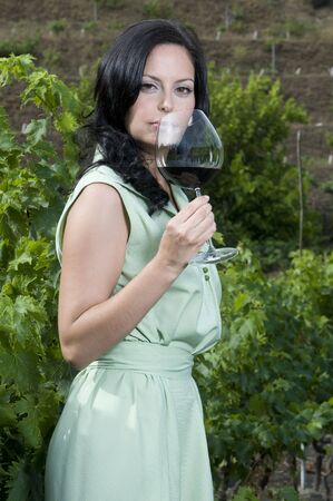 woman tasting a glass of red wine in a vineyard photo