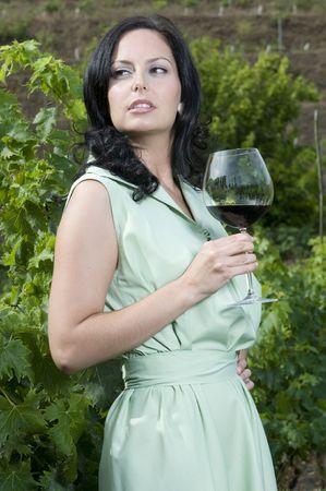 beauty woman having a glass of wine in a vineyard photo