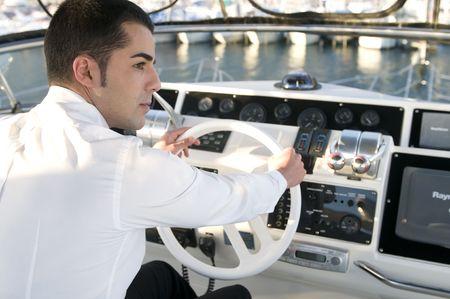 capitan de barco: el hombre elegante j�venes en el yate de control de Foto de archivo