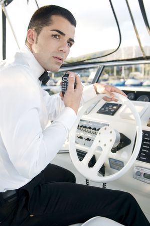 young elegant man at yatch control