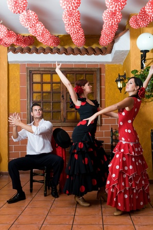 men and women in traditional flamenco dresses dance during the Feria de Abril on April photo