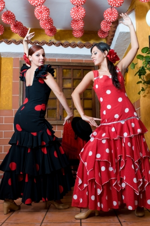 women in traditional flamenco dresses dance during the Feria de Abril on April Stock Photo