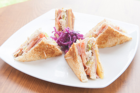 turkey bacon: club sandwich made with turkey, bacon, ham, tomato, cheese, lettuce, and garnished with a pickle and two cherry tomatoes