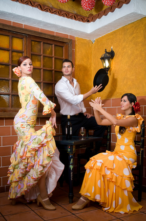 women and man in traditional flamenco dresses dance during the Feria de Abril on April Spain photo