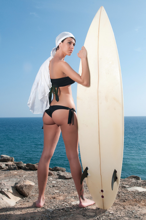 woman with surfboard waiting for waves photo