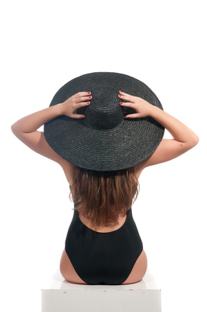 back of woman with hat in white photo
