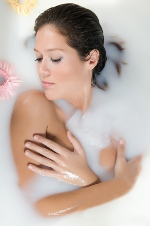 woman relaxing in milk bath with flowers Stock Photo