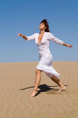 Beautiful woman walking in the desert photo
