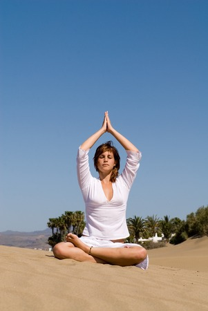 young girl on the sand in yoga photo