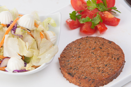 bap: vegetarian burger made from vegetables and breadcrumbs, stacked with onion rings, slice of tomato