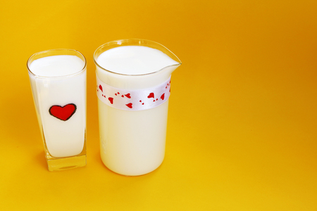 A Jug and glass of milk on yellow background, Milk concept